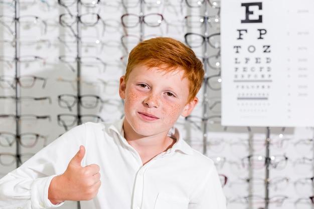 Retrato de niño sonriente mostrando pulgar arriba gesto mirando a la cámara Foto gratis