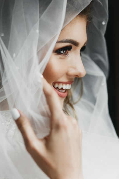 Retrato de novia encantadora envuelta en un velo. Foto gratis