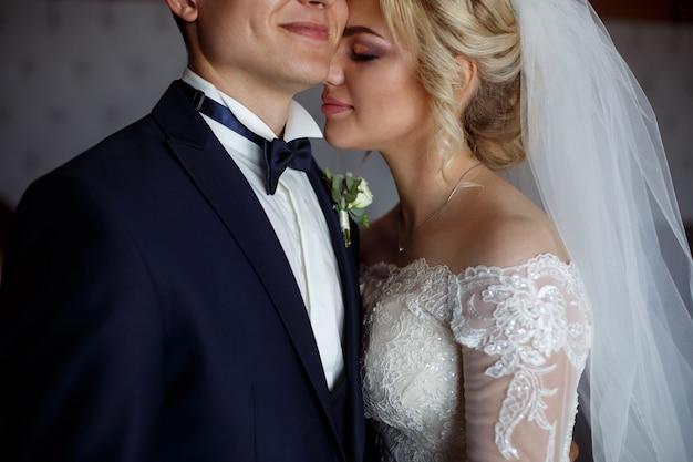 Retrato de novios de cerca. retrato de un amoroso recién casados. la novia abraza suavemente y besa al novio. día de la boda. retrató una feliz pareja de enamorados en el interior Foto Premium