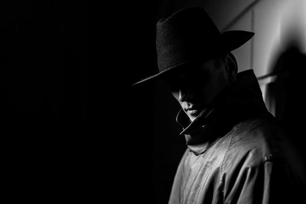 Retrato oscuro de un hombre con un impermeable con sombrero por la noche en  la calle en un estilo crimen noir | Foto Premium