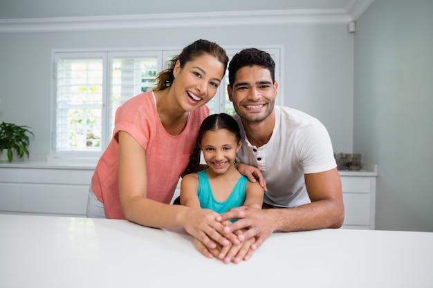 Retrato de padres e hija de pie juntos en la cocina Foto Premium