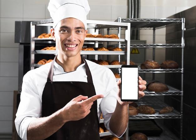 Retrato de un panadero de sexo masculino joven sonriente que muestra el teléfono móvil delante de estantes cocidos del cruasán Foto gratis