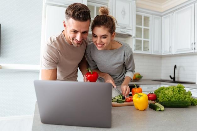 Retrato de una pareja amorosa alegre cocinar ensalada juntos Foto gratis