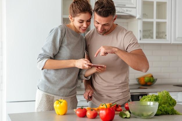 Retrato de una pareja amorosa sonriente cocinar ensalada juntos Foto gratis