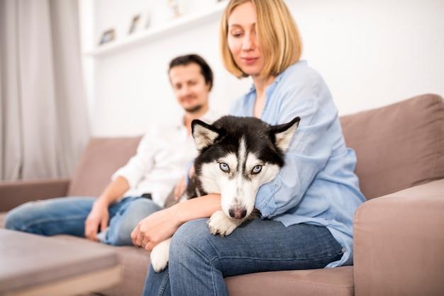 Retrato de pareja feliz en casa con perro Foto gratis