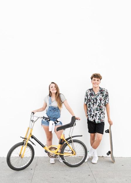 Retrato de una pareja feliz de pie con bicicleta y patineta delante de la pared Foto gratis