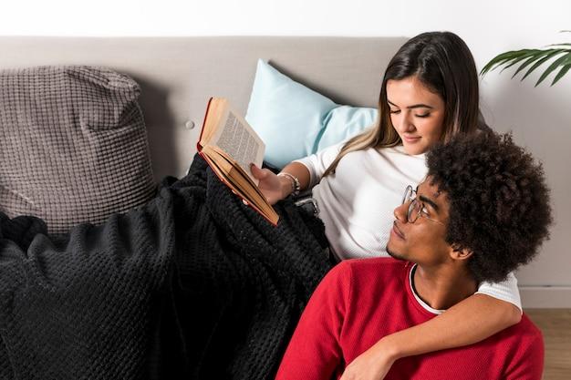Retrato de pareja interracial leyendo juntos Foto gratis