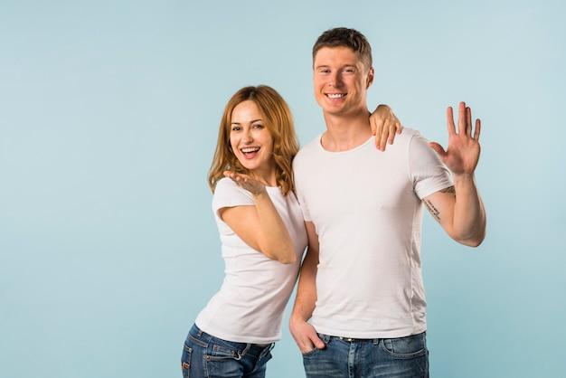 Retrato de una pareja joven sonriente agitando las manos contra el fondo azul Foto gratis