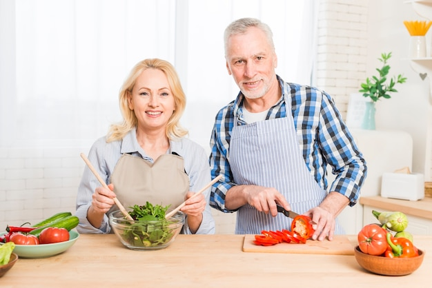Retrato de una pareja senior preparando la comida en la cocina Foto gratis