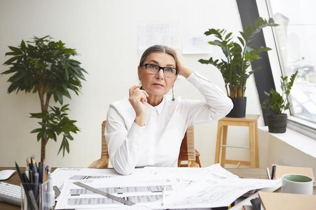 Retrato de pensativa arquitecta de pelo gris de unos cincuenta años tocando la cabeza mientras trabajaba en su escritorio de oficina, haciendo dibujos con herramientas arquitectónicas, mirando hacia arriba, buscando inspiración Foto gratis