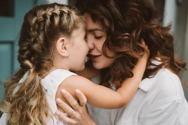 Retrato de pequeña hija besando a su hermosa madre feliz Foto gratis