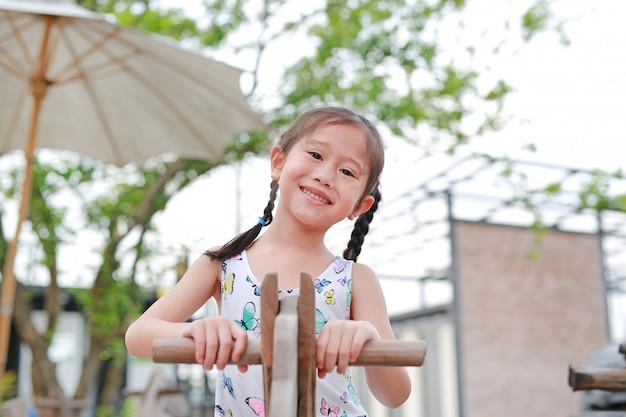 Retrato de la peque a muchacha asi tica feliz que juega el for Jardin al aire libre de madera deco