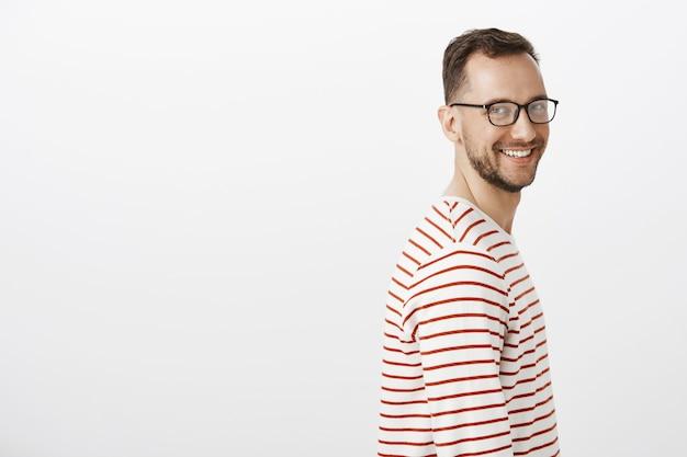 Retrato de perfil de chico caucásico de aspecto amable despreocupado con barba en gafas negras Foto gratis