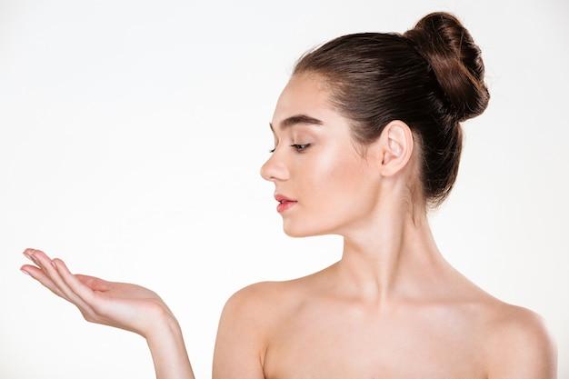 Retrato de perfil de hermosa mujer joven con piel fresca posando mostrando producto en su espacio de copia de palma Foto gratis