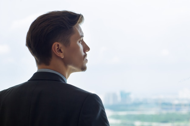 Retrato de perfil de hombre serio mirando por la ventana Foto gratis
