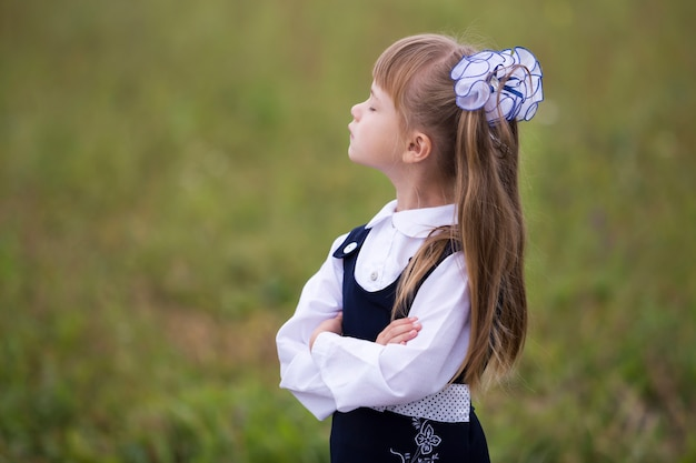 Retrato de perfil de niña adorable linda de primer grado en uniforme escolar y lazos blancos Foto Premium