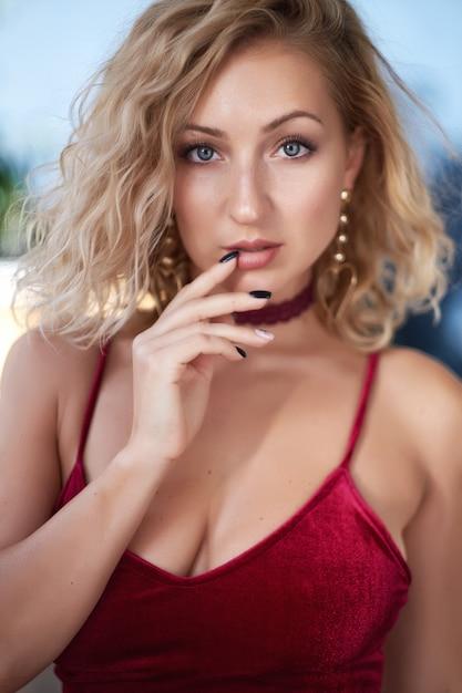 Retrato del primer de una mujer joven rubia hermosa que mira la cámara. Foto Premium