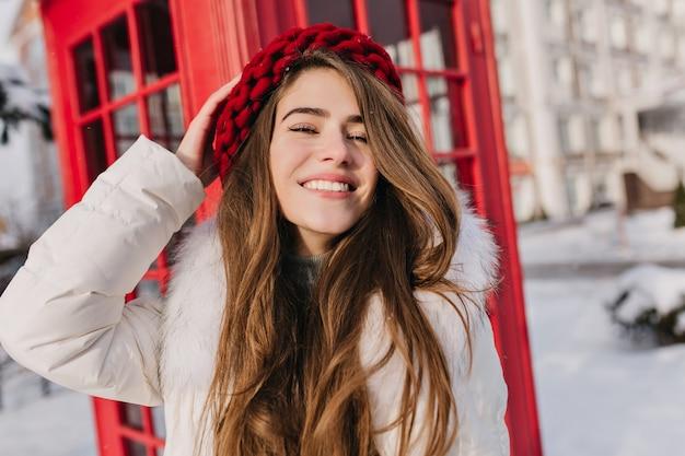 Retrato de primer plano de la alegre mujer de pelo largo con sombrero rojo posando delante de la cabina telefónica. foto al aire libre de la encantadora dama europea en boina tejida de pie junto a la cabina. Foto gratis