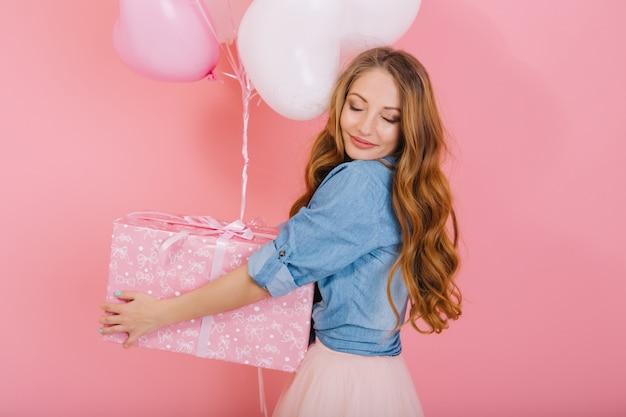 Retrato de primer plano de la elegante niña rizada con cara encantadora sosteniendo globos para el cumpleaños de un amigo. encantadora joven de pelo largo con los ojos cerrados en elegante traje recibió regalo en la fiesta Foto gratis