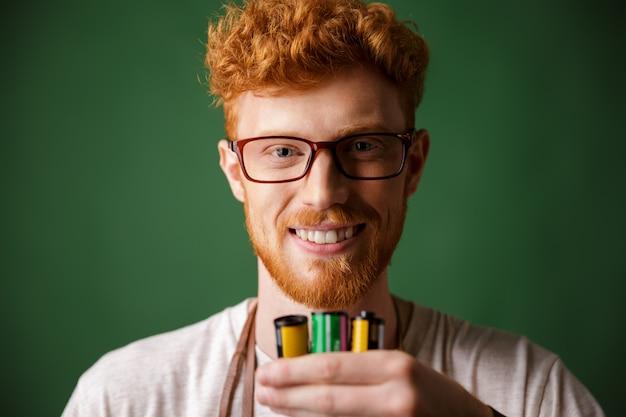 Retrato de primer plano del fotógrafo barbudo de cabeza lectora con gafas, sosteniendo rollos de cámara Foto gratis
