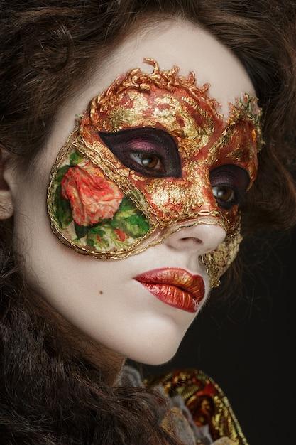 Retrato de primer plano de hermosa mujer en vestido vintage y una máscara en su rostro. Foto Premium