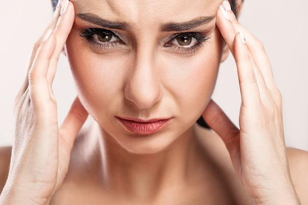 Retrato de primer plano de una hermosa niña enferma que sufre de dolor de cabeza Foto Premium