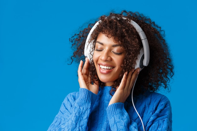 Retrato de primer plano tierno y despreocupado feliz, sonriente, mujer afroamericana sensual con auriculares grandes, ojos cerrados y sonrisa romántica recordar buenos recuerdos de escuchar canción, azul Foto Premium