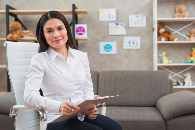 Retrato del psicólogo de sexo femenino sonriente que se sienta en la silla blanca con el tablero y el lápiz en su oficina Foto Premium