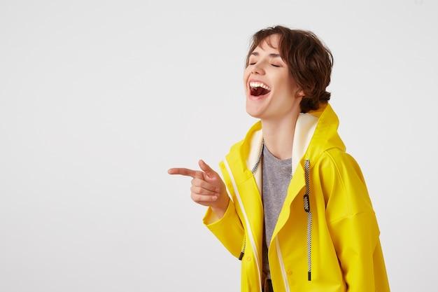El retrato de la risa joven feliz linda de pelo corto viste un impermeable amarillo, sonríe ampliamente, escucha chistes divertidos, se para sobre la pared blanca y señala el espacio de la copia a la izquierda. Foto gratis