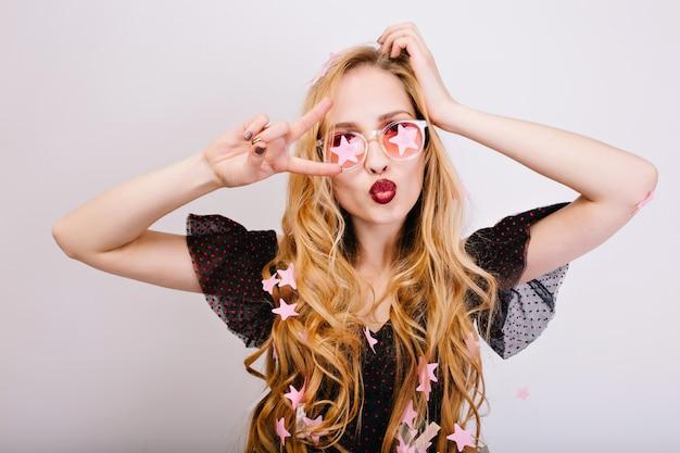 Retrato de rubia alegre con pelo largo y rizado divirtiéndose en la fiesta, haciendo muecas, mostrando paz, beso, disfrutando de la celebración. lleva un vestido negro, gafas rosas. aislado.. Foto gratis
