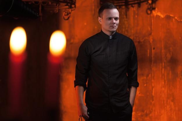 Retrato del sacerdote o del pastor católico hermoso con el collar de perro, fondo rojo oscuro. Foto Premium