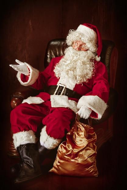 Retrato de santa claus en traje rojo sentado en un sillón Foto gratis