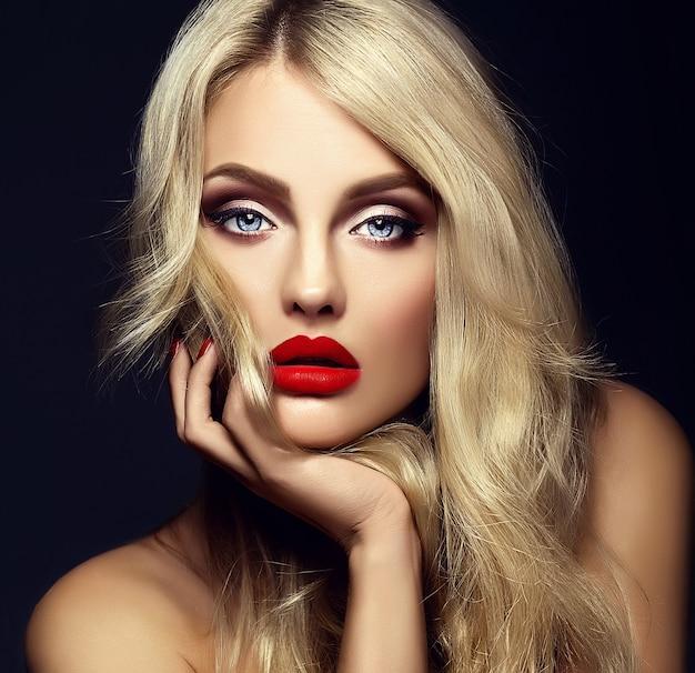 Retrato sensual glamour de hermosa mujer rubia modelo dama con maquillaje brillante y labios rojos tocando su rostro, con cabello rizado saludable sobre fondo negro Foto gratis