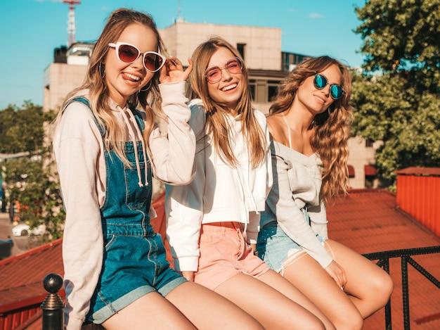 Retrato de sexy mujer despreocupada sentada en la barandilla de la calle. modelos positivos divirtiéndose en gafas de sol Foto gratis