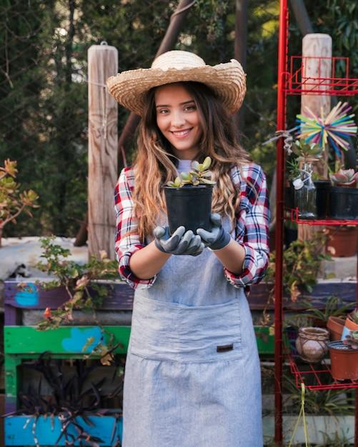 Retrato de un sombrero que lleva sonriente del jardinero de sexo femenino que muestra la planta del cactus en el jardín Foto gratis