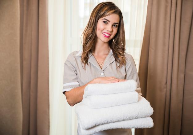 Retrato sonriente de la camarera joven que sostiene limpio doblado apilado de la toalla suave a disposición Foto gratis