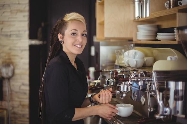 Retrato de sonriente camarera preparando una taza de café Foto gratis