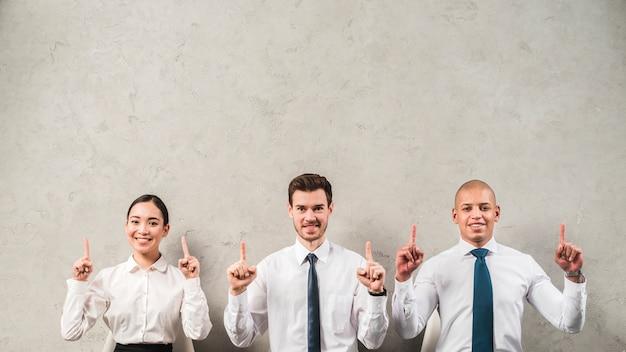 Retrato sonriente de una empresaria y un hombre de negocios que señalan sus dedos hacia arriba contra la pared gris Foto gratis