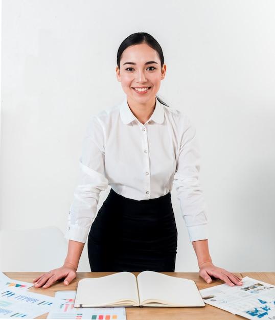 Retrato sonriente de una empresaria joven que se coloca detrás del escritorio contra la pared blanca Foto gratis