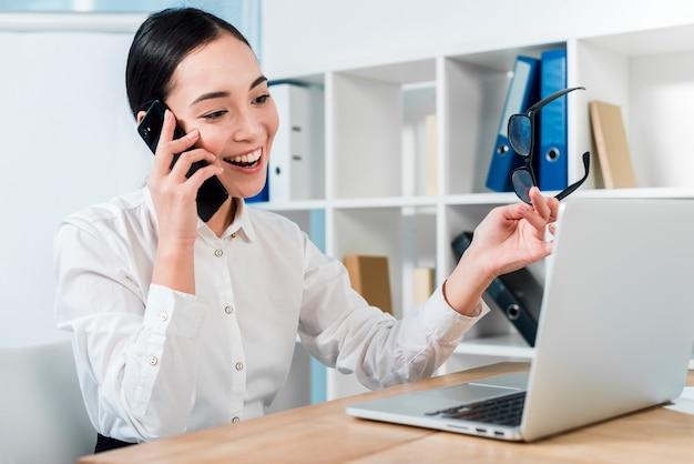 Retrato sonriente de una empresaria joven que habla en el teléfono móvil que mira el ordenador portátil Foto gratis