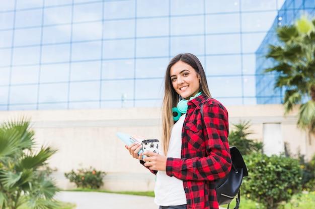 Retrato sonriente de un estudiante joven que sostiene los libros y la taza de café para llevar que se coloca delante del edificio de la universidad Foto gratis