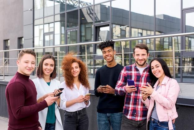 Retrato sonriente de estudiantes jóvenes alegres que usan teléfonos inteligentes de pie fuera de los edificios Foto gratis