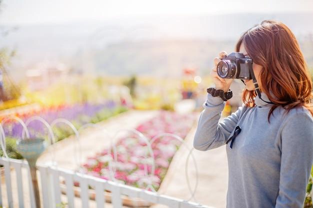 Retrato sonriente de la forma de vida del verano al aire libre de la mujer bastante joven que se divierte en el jardín.