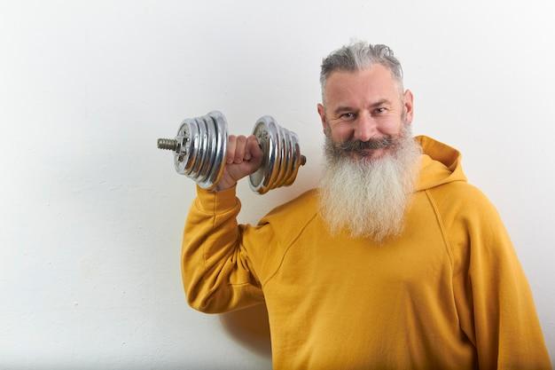 Retrato de sonriente hombre barbudo maduro con mancuernas en casa Foto Premium