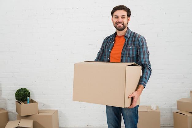 Retrato sonriente de un hombre joven que lleva la caja de cartón que se opone a la pared blanca Foto gratis