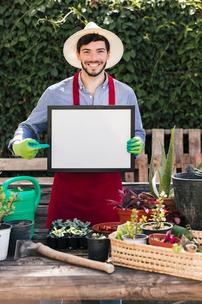 Retrato sonriente de un hombre joven que está parado detrás de las plantas en maceta que señalan el dedo en el marco en blanco blanco Foto gratis