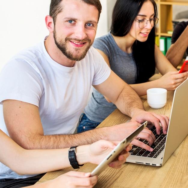 Retrato sonriente de un hombre joven que trabaja en la computadora portátil sobre el escritorio de madera Foto gratis