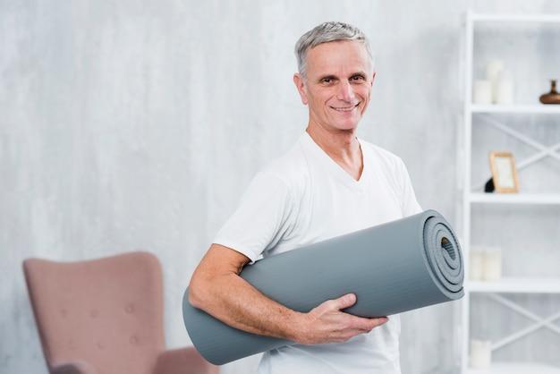 Retrato sonriente de un hombre que sostiene la estera rodada de la yoga en casa Foto gratis