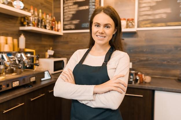 Retrato de sonriente joven dueño de cafetería femenina Foto Premium