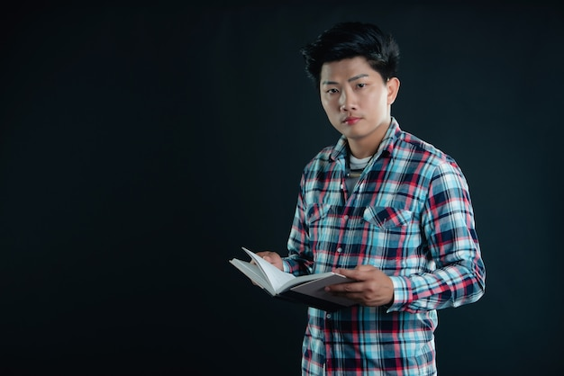 Retrato de sonriente joven estudiante universitario con libros Foto gratis
